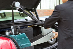 compact electric scooter being placed in car trunk